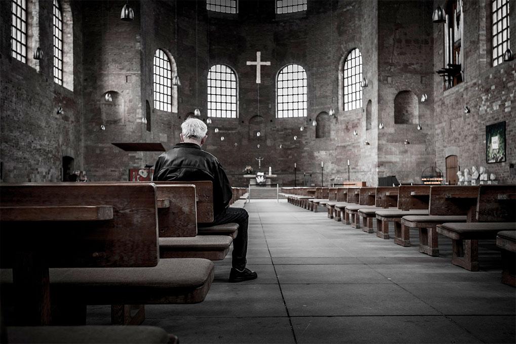 hombre mayor en iglesia reflexionando