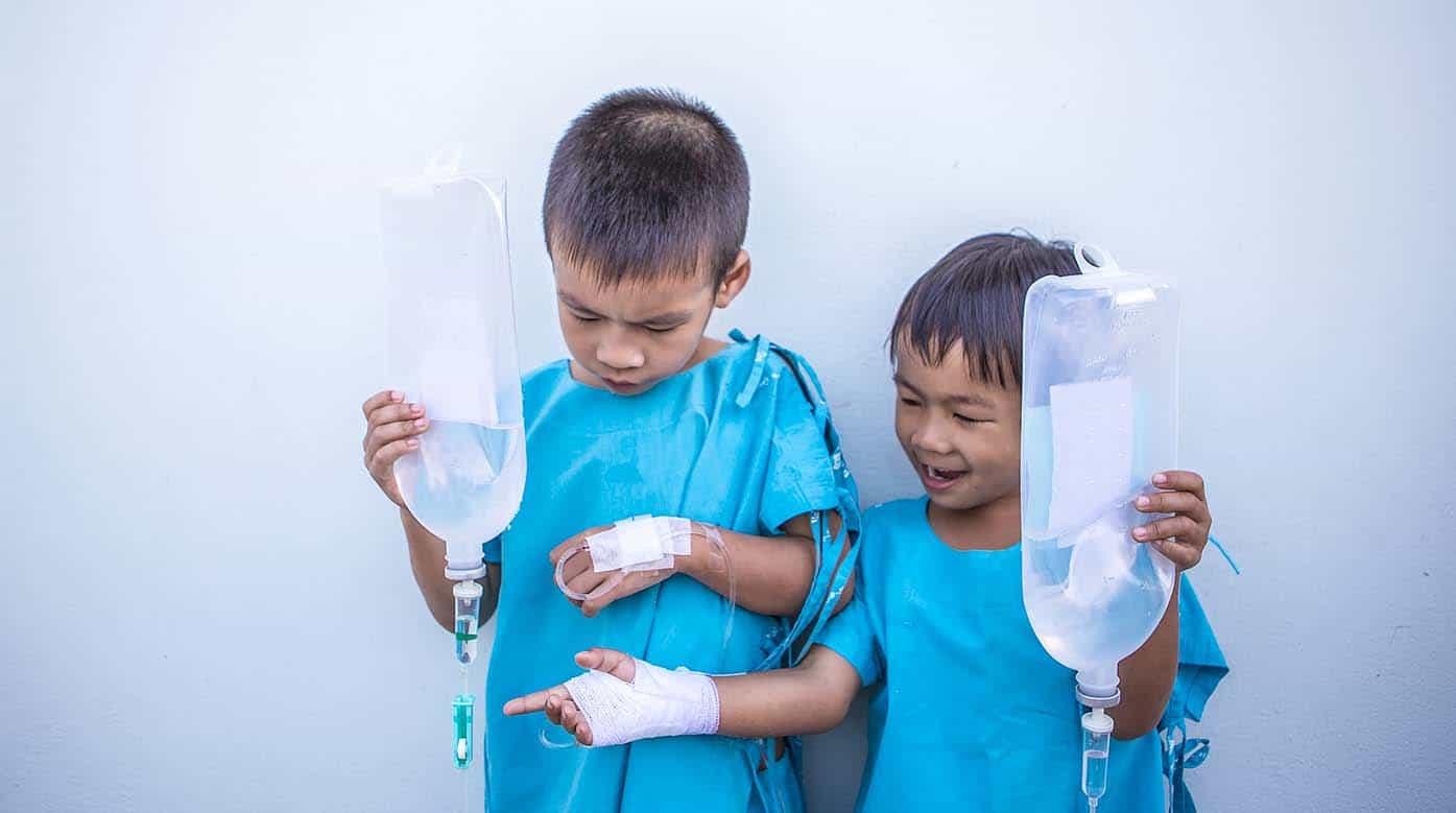 niños enfermos con vendas en las manos riendo