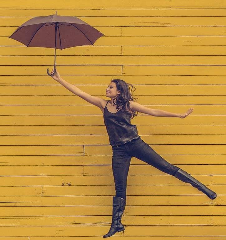 mujer feliz simulando que vuela con un paraguas