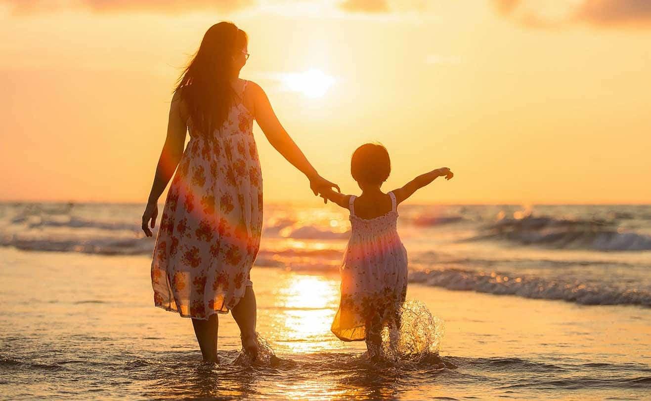 mamá e hija caminando por la playa