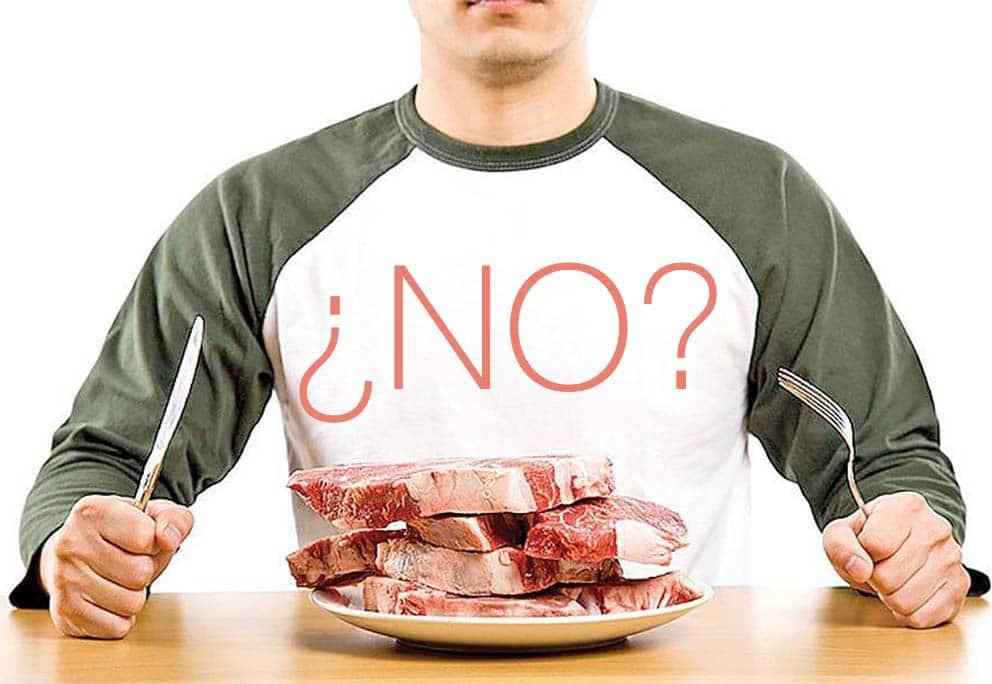 persona sentada frente a la mesa con un plato de carne pensando si se la come